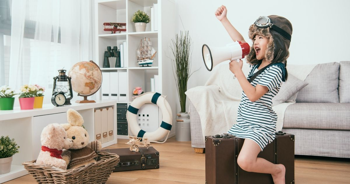 Fun images of young girl sitting on suitcase and shouting on megaphone.