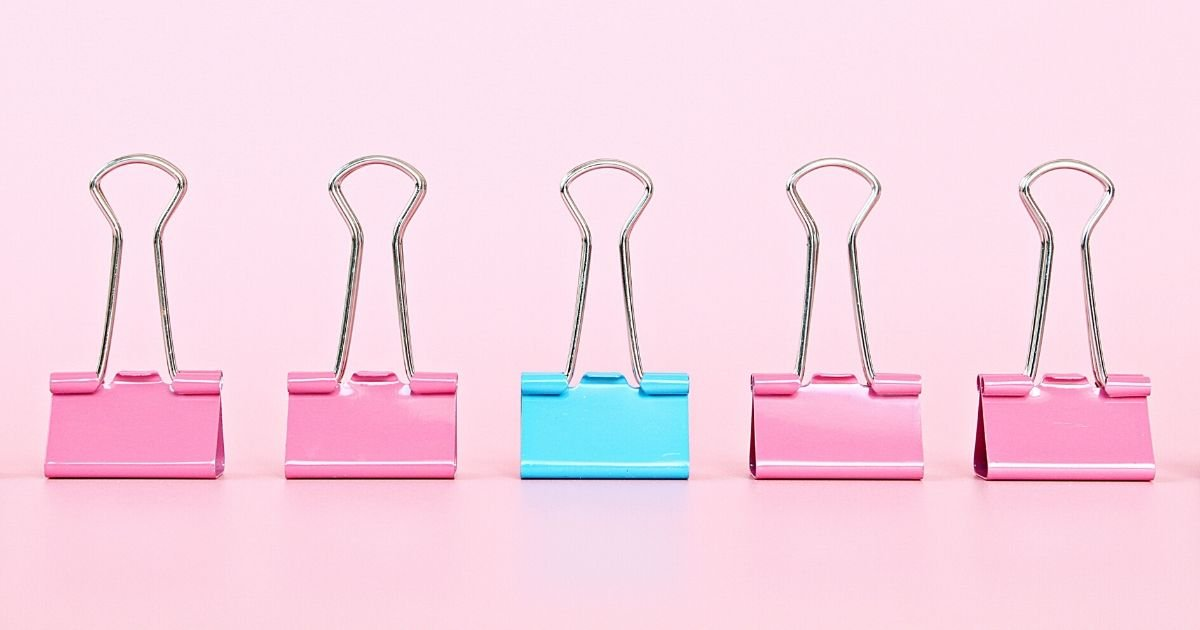 A blue foldback clip amongst 4 pink foldback clips.