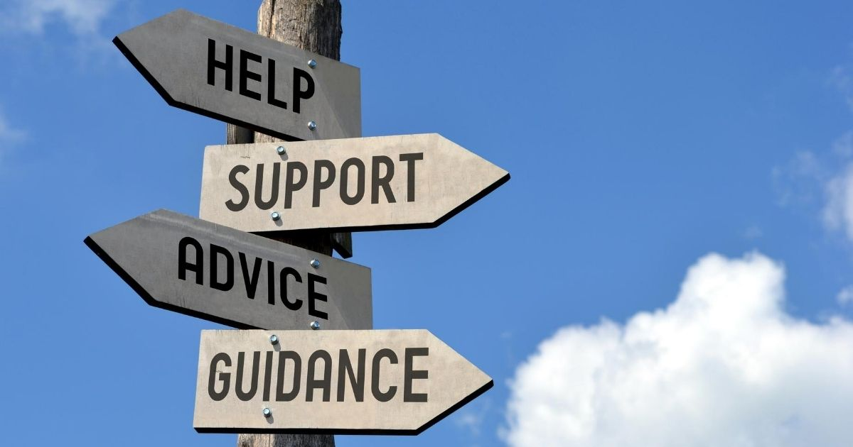 Wooden sign showing help, support, advice and guidance.